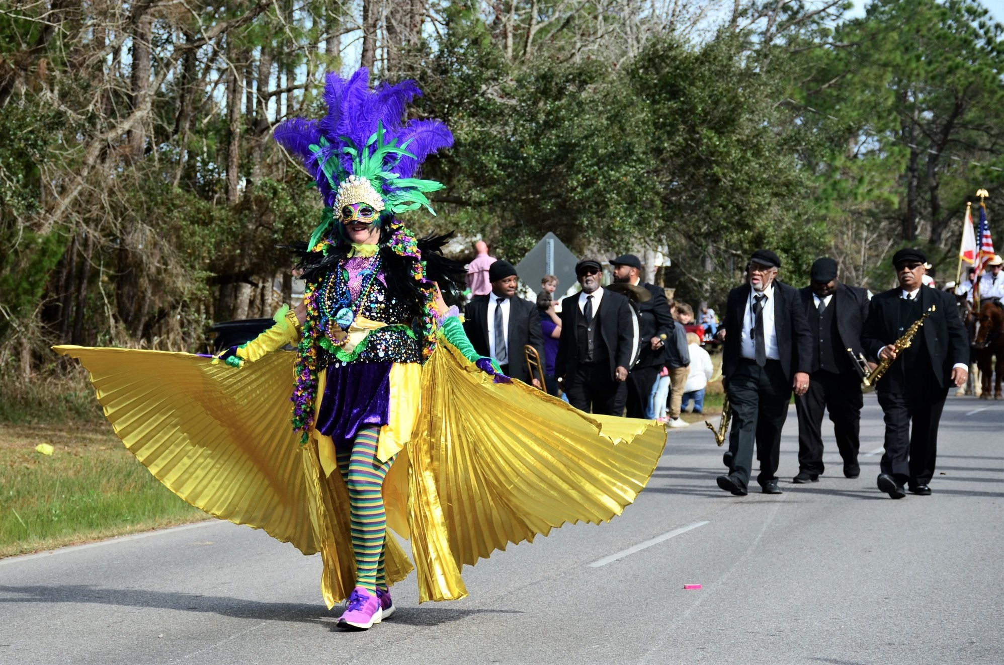 woman covered in beads and feathers celebrates by walking the mardi gras parade